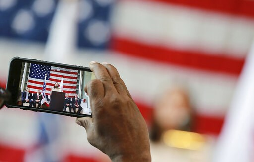 (AP Photo/Eugene Hoshiko, File). FILE - Aug. 2, 2017, file photo, a guest takes a video of U.S. Olympic Committee chief marketing officer Lisa Baird speaking at the Tokyo American Club in Tokyo. The U.S. Olympic Committee tabbed Paralympic executive Ri...