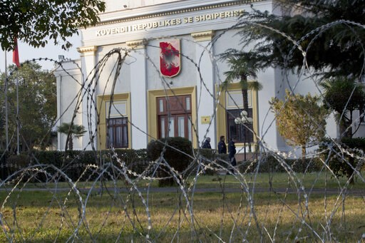 (AP Photo/Visar Kryeziu). Policemen are seen behind barbwire placed to secure the Parliament building as opposition supporters gather to participate in an anti-government rally in capital Tirana, Albania, on Tuesday, Feb. 21, 2019.  Albania's oppositio...