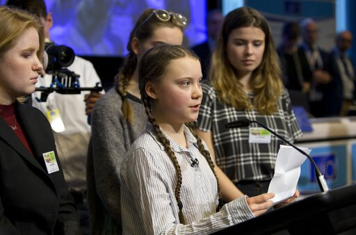 (AP Photo/Virginia Mayo). Swedish climate activist Greta Thunberg, center, speaks during an event at the EU Charlemagne building in Brussels, Thursday, Feb. 21, 2019. Thunberg will also participate in a climate march through the city later in the day.