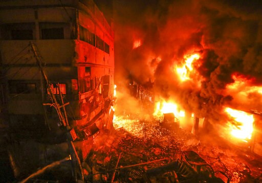 (AP Photo/Zabed Hasnain Chowdhury). Flames rise from a fire in a densely packed shopping area in Dhaka, Bangladesh, Thursday, Feb. 21, 2019. A devastating fire raced through at least five buildings in an old part of Bangladesh's capital and killed scor...