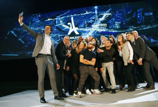(AP Photo/Michel Euler). Paris 2024 Games' chief Tony Estanguet, left, makes a selfie with all invited guests after a media conference at La Defense business district, outside Paris, Thursday, Feb. 21 , 2019. The organizers of the 2024 Paris Olympics w...