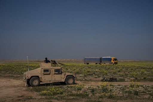 (AP Photo/Felipe Dana). A U.S.-backed Syrian Democratic Forces (SDF) Humvee stands by as a truck that is part of a convoy evacuating hundreds out of the last territory held by Islamic State militants, passes in Baghouz, eastern Syria, Wednesday, Feb. 2...