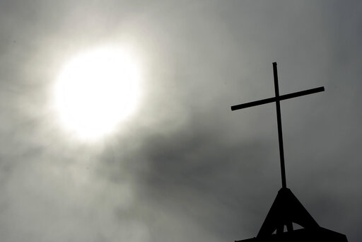 (AP Photo/Markus Schreiber, File). FILE - In this April 8, 2010 file photo a cross sits on top of a church in Berlin, Germany. In September 2018, the German Catholic Church released a devastating report that concluded at least 3,677 people were abused ...