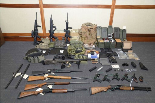 (U.S. District Court via AP). This image provided by the U.S. District Court in Maryland shows a photo of firearms and ammunition that was in the motion for detention pending trial in the case against Christopher Paul Hasson. Prosecutors say that Hasso...