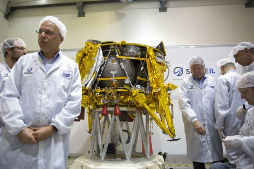 (AP Photo/Ariel Schalit). FILE - In this Monday, Dec. 17, 2018 file photo, technicians stand next to the SpaceIL lunar module, an unmanned spacecraft, on display in a special clean room during a press tour of their facility near Tel Aviv, Israel. Space...