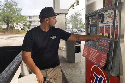 (AP Photo/Grace Garces Bordallo). Jared Duenas fills up his pickup truck with gasoline in the village of Sinajana, Guam in preparation of a typhoon on Thursday, Feb. 21, 2019.  An intensifying tropical storm in the Pacific is bearing down on Micronesia...