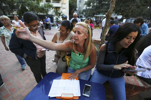 (AP Photo/Fernando Llano). In this Feb. 19. 2019 photo, people fill forms to joint to the group of volunteers that will help to introduce humanitarian aid into Venezuela, during a meeting to recruit volunteers, at a square in Caracas, Venezuela. The op...