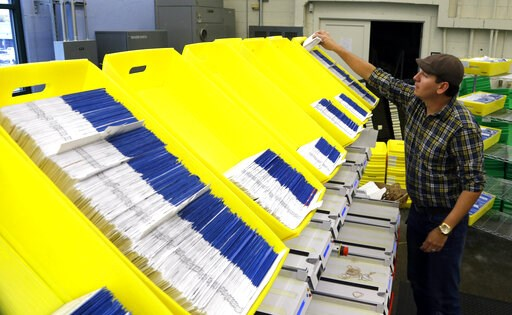 (AP Photo/Don Ryan, File). FILE - In this Nov. 3, 2014, file photo, Diego Valencia processes Oregon ballots at Multnomah County election headquarters in Portland, Ore. Oregon Gov. Kate Brown is touting a new report that found nearly 78,000 Oregonians w...