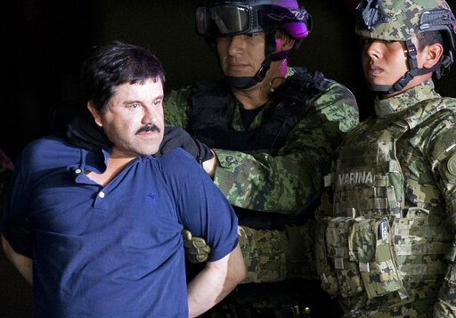 """(AP Photo/Eduardo Verdugo, File). FILE - In this Jan. 8, 2016 file photo, a handcuffed Joaquin """"El Chapo"""" Guzman is made to face the press as he is escorted to a helicopter by Mexican soldiers and marines at a federal hangar in Mexico City. Guzman was ..."""