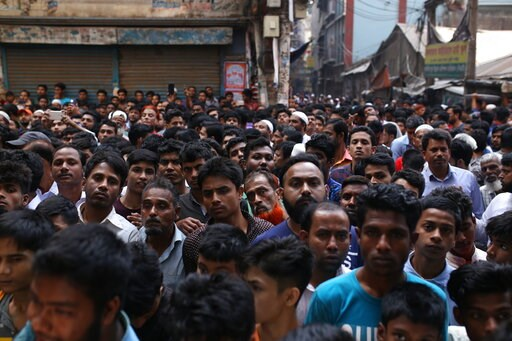 (AP Photo/Rehman Asad). A crowd gathers at the site of a fire accident in Dhaka, Bangladesh, Thursday, Feb. 21, 2019. A devastating fire raced through at least five buildings in an old part of Bangladesh's capital and killed scores of people.