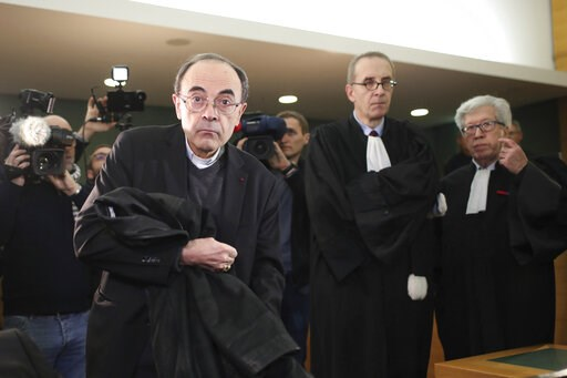 (AP Photo/Laurent Cipriani, File). FILE - In this Jan.7, 2019 file photo, cardinal Philippe Barbarin, center, takes his seat as he arrives at the Lyon courthouse with his lawyers : Jean-Felix Luciani, 2nd right, and Andre Soulier, right, to attend his ...