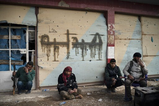 (AP Photo/Felipe Dana, File). FILE - In this Saturday, Feb. 16, 2019 file photo, U.S.-backed Syrian Democratic Forces  fighters take a break as the fight against Islamic State militants continues in the village of Baghouz, Syria. U.S. and Iraqi officia...