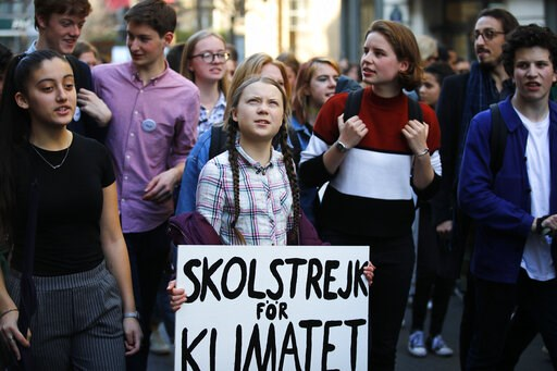"""(AP Photo/Francois Mori). Swedish teenager Greta Thunberg, center, leads a march of thousands of French students through Paris, France, to draw more attention to fighting climate change, Friday, Feb. 22, 2019. Sign reads : """"school strike for the climat..."""