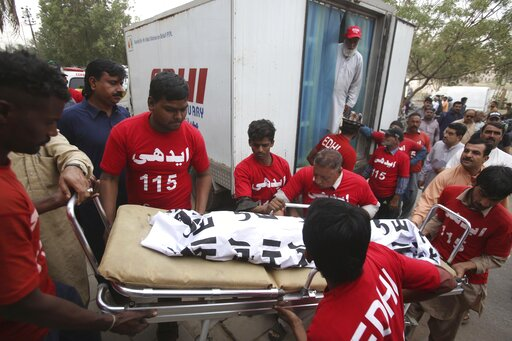 (AP Photo/Fareed Khan). Pakistani volunteers move the body of a food poisoning victim to a mortuary in Karachi, Pakistan, Friday, Feb. 22, 2019. Pakistani police say many children have died of suspected food poisoning after their family had dinner at a...