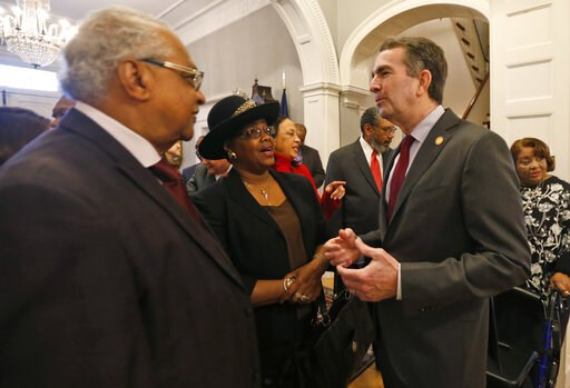 (AP Photo/Steve Helber). Virginia Gov. Ralph Northam greets, a member of the Richmond 34, Leroy Bray and his wife Cynthia, center, for a breakfast at the Governors Mansion at the Capitol in Richmond, Va., Friday, Feb. 22, 2019. The Richmond 34 were a g...