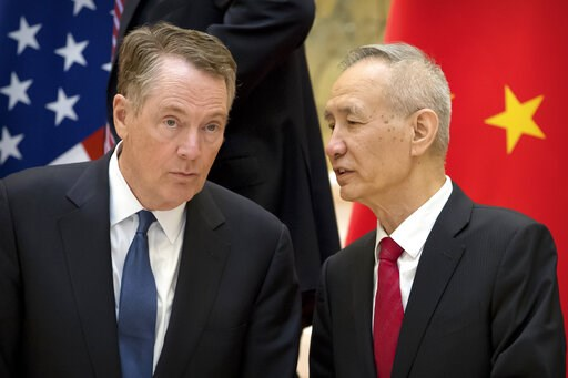 (AP Photo/Mark Schiefelbein, File). FILE - In this Feb. 15, 2019, file photo, Chinese Vice Premier Liu He, right, talks with U.S. Trade Representative Robert Lighthizer, while they line up for a group photo at the Diaoyutai State Guesthouse in Beijing....