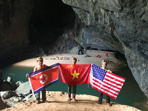 (Oxalis Adventure via AP). In this Monday, Feb. 15, 2019, drone image, cave explores pose with flags of North Korea, Vietnam and the U.S. in En cave in Quang Binh province, Vietnam. Vietnam will host the second summit between U.S. President Donald Trum...