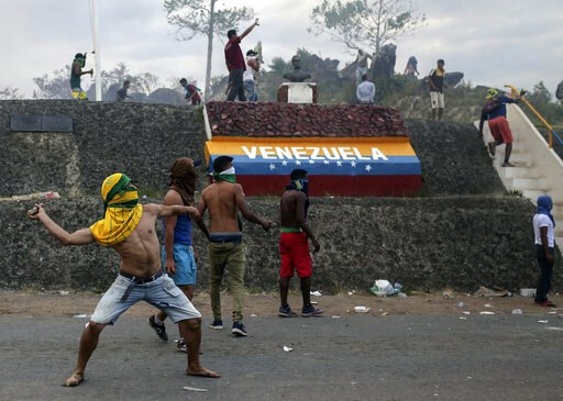 (AP Photo/Ivan Valencia). Venezuelan demonstrators throw stones during clashes with authorities, at the border between Brazil and Venezuela, Saturday, Feb.23, 2019. Tensions are running high in the Brazilian border city of Pacaraima. Thousands remained...