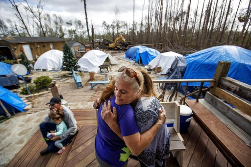 """(AP Photo/David Goldman). Diahnn """"Shelly"""" Summers, right, embraces Lori Hogan, who is currently living in a tent in Summers' backyard months after Hurricane Michael hit in Youngstown, Fla, Wednesday, Jan. 23, 2019. """"This is the first time I've felt com..."""
