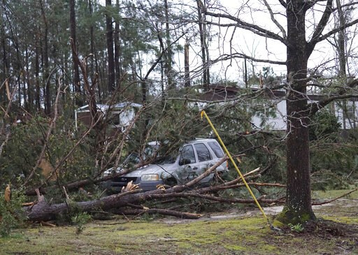 (Kara Coleman Fields/Opelika-Auburn News via AP). A vehicle is caught under downed trees along Lee Road 11 in Beauregard, Ala., Sunday, March 3, 2019, after a powerful storm system passed through the area.