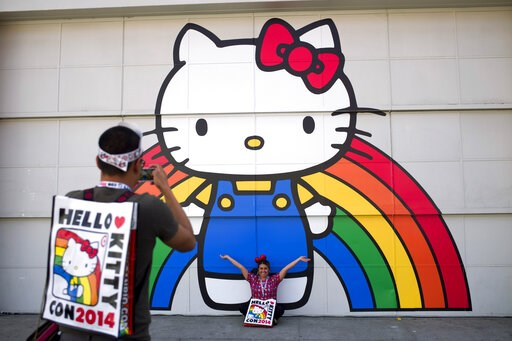 (AP Photo/Jae C. Hong, File). FILE - In this Oct. 30, 2014, file photo, Keith Nunez, left, takes pictures of his wife, Carolina, at the first-ever Hello Kitty fan convention, Hello Kitty Con, at the Geffen Contemporary at MOCA in Los Angeles. Hello Kit...
