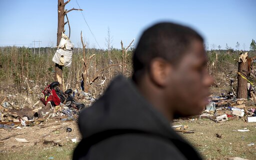 (AP Photo/David Goldman). Demetria Jones walks through the damaged neighborhood where he said he lost ten relatives in a tornado in Beauregard, Ala., Tuesday, March 5, 2019.