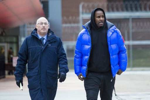 (Ashlee Rezin/Chicago Sun-Times via AP, File). FILE - In this Monday, Feb. 25, 2019 file photo, R. Kelly walks out of Cook County Jail with his defense attorney, Steve Greenberg, after posting $100,000 bail, in Chicago. In his first interview since bei...