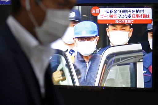 (Akiko Matsushita/Kyodo News via AP). A man walks by a TV monitor which reports on former chairman of Nissan Motor Co., Carlos Ghosn, in Tokyo Wednesday, March 6, 2019. Disguised as a construction worker, Ghosn left a Tokyo detention center Wednesday a...