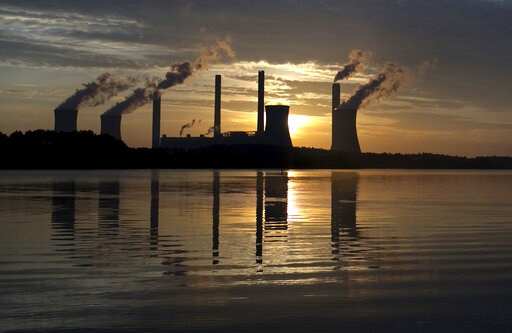 (AP Photo/Branden Camp, File). FILE - In this June, 3, 2017, file photo, the sun sets behind Georgia Power's coal-fired Plant Scherer, one of the nation's top carbon dioxide emitters, in Juliette, Ga. As climate change becomes a hotter topic in America...