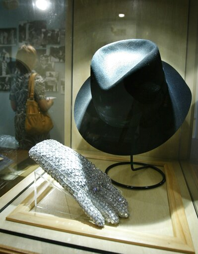 (AP Photo/Carlos Osorio). FILE - In this June 21, 2010 file photo, a hat and sequined glove once belonging to Michael Jackson is displayed at the Motown Historical Museum at Hitsville U.S.A. in Detroit. Some fans may be removing Michael Jackson's music...