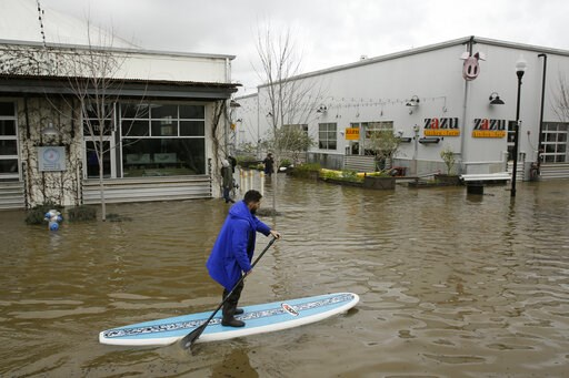 (AP Photo/Eric Risberg). FILE - In this Wednesday, Feb. 27, 2019 file photo, a man uses a paddle board to make his way through the flooded Barlow Market District in Sebastopol, Calif. On Wednesday, March 6, 2019, the National Oceanic and Atmospheric Ad...