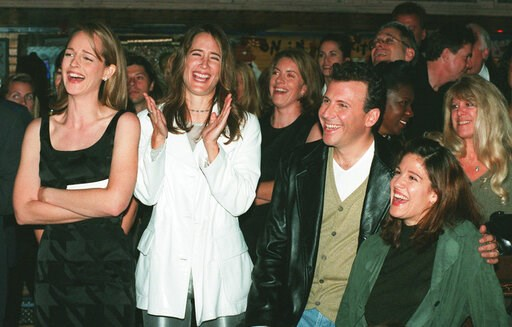 """(AP Photo/Chris Pizzello, File). In this Nov. 11, 1996, file photo, """"Mad About You"""" cast members Helen Hunt, from left, Anne Ramsay, Paul Reiser and Reiser's wife Paula laugh at a satiric video made by the show's crew during a private party at the Hous..."""