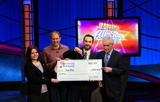 """(Carol Kaelson /Sony via AP). This photo provided by Sony shows Brad Rutter, Larissa Kelly and David Madden with Alex Trebek, winners of the first-ever """"Jeopardy!"""" team championship, Tuesday, March 5, 2019 in in Burbank, Calif. With $1 million at stake..."""