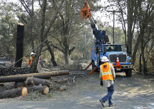 (AP Photo/Ben Margot, File). FILE - In this Oct. 18, 2017 file photo, a Pacific Gas & Electric crew works on replacing poles destroyed by wildfires in Glen Ellen, Calif. A U.S. judge in San Francisco overseeing a criminal case against Pacific Gas &...