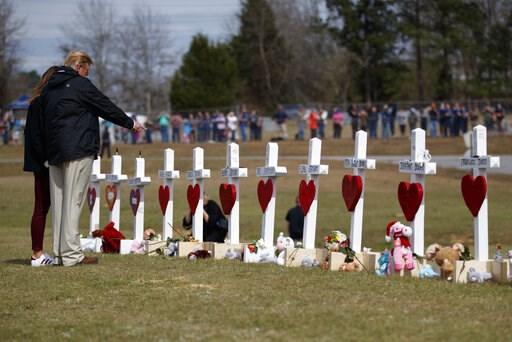 (AP Photo/Carolyn Kaster). President Donald Trump and first lady Melania Trump pause at a line of crosses outside Providence Baptist Church in Smiths Station, Ala., Friday, March 8, 2019, during a tour of areas where tornados killed 23 people in Lee Co...