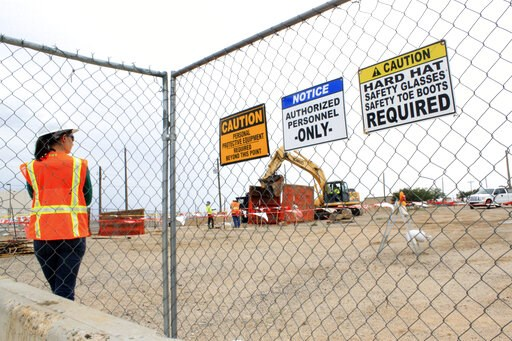 (AP Photo/Susan Montoya Bryan). FILE - This Aug. 7, 2014, image shows a contract employee watching a crews excavate contaminated soil at a site where millions of gallons of jet fuel leaked underground over decades at Kirtland Air Force Base in Albuquer...