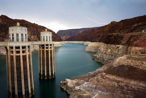 (AP Photo/John Locher, File). FILE - In this July 28, 2014, file photo, lightning strikes over Lake Mead near Hoover Dam that impounds Colorado River water at the Lake Mead National Recreation Area in Arizona. A major southern California utility is pos...