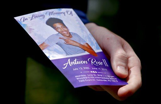 (AP Photo/Keith Srakocic, File). File-In this file photo from June 25, 2018, Kyle Fogarty shows a memorial card of Antwon Rose II after the funeral in Swissvale, Pa. Rose was fatally shot by a police officer seconds after he fled a traffic stop June 19...