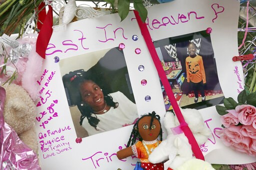 (AP Photo/Reed Saxon). Photos adorn a large memorial to Trinity Love Jones, the 9-year-old girl whose body was found in a duffel bag along a suburban Los Angeles equestrian trail, in Hacienda Heights, Calif., Monday, March 11, 2019. Two people have bee...