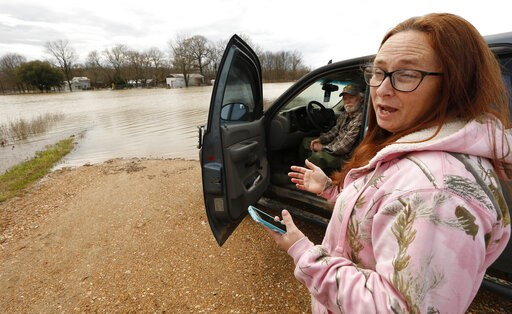 "(AP Photo/Rogelio V. Solis). In this Monday, March 11, 2019 photo, Peggy and her husband George Sellars sit by the ""lake"" that was the driveway to their home, along Mississippi 16, east of Rolling Fork, Miss. The couple said the backwater flooding is t..."