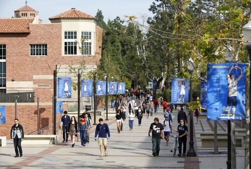 (AP Photo/Damian Dovarganes, File). FILE - In this Feb. 26, 2015, file photo, students walk on the University of California, Los Angeles campus. Federal authorities have charged college coaches and others in a sweeping admissions bribery case in federa...