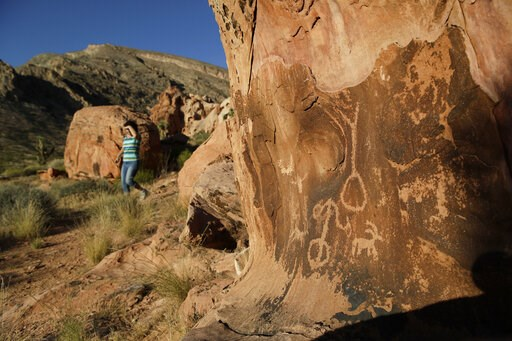 (AP Photo/John Locher, File). FILE - In this May 26, 2017, file photo, Susie Gelbart walks near petroglyphs at the Gold Butte National Monument near Bunkerville, Nev. As Democrats in Congress prepare to scrutinize President Donald Trump's review of 27 ...