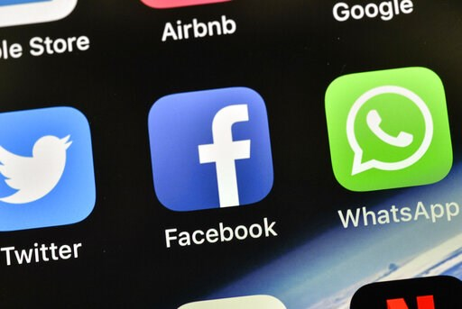 (AP Photo/Martin Meissner, File). FILE - In this Nov. 15, 2018, file photo the icons of Facebook and WhatsApp are pictured on an iPhone in Gelsenkirchen, Germany. Facebook is already the leader in enabling you to share photos, videos and links. It now ...