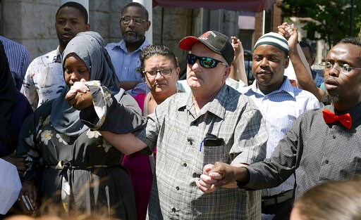 (Daryn Slover/Sun Journal via AP, File). FILE - In this June 17, 2018, file photo, Jim Thompson, center, of Auburn, Maine, holds hands with Fowsia Musse, left, and Abdi Abdalla during a gathering to lessen rising ethnic tensions in Lewiston, Maine. Tho...