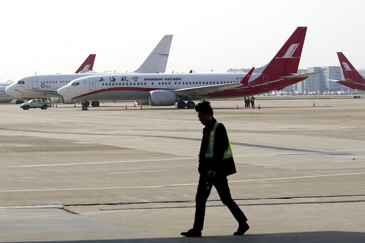 (AP Photo). A ground crew walks near a Boeing 737 Max 8 plane operated by Shanghai Airlines parked on the tarmac at Hongqiao airport in Shanghai, China, Tuesday, March 12, 2019. U.S. aviation experts on Tuesday joined the investigation into the crash o...