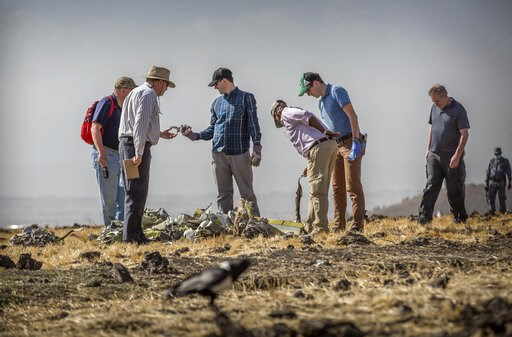 (AP Photo/Mulugeta Ayene). Foreign investigators examine wreckage at the scene where the Ethiopian Airlines Boeing 737 Max 8 crashed shortly after takeoff on Sunday killing all 157 on board, near Bishoftu, or Debre Zeit, south of Addis Ababa, in Ethiop...