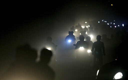 (AP Photo/Altaf Qadri). FILE - In this Friday, Nov. 10, 2017 file photo, motorists ride through a thick blanket of smog and dust on the outskirts of New Delhi, India., with microscopic particles spiking at times to 75 times the level considered safe by...