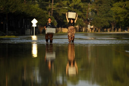 (AP Photo/Gregory Bull). FILE - In this Monday, Sept. 4, 2017 file photo, Mariko Shimmi, right, helps carry items out of the home of Ken Tani in a neighborhood still flooded from Harvey in Houston. Some neighborhoods around Houston remain flooded and t...