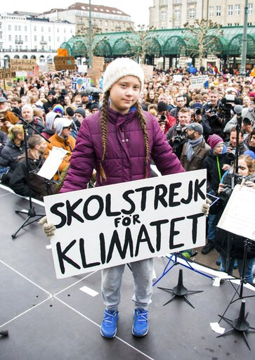 (Daniel Reinhardt/dpa via AP). Swedish climate activist Greta Thunberg holds a protest poster as she attends a protest rally in Hamburg, Germany, Friday, March 1, 2019. Slogan reads 'School Strike For The Climate'.