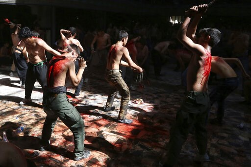 (AP Photo/Rahmat Gul). FILE - In this Sunday, Oct. 9, 2016 file photo, Shiite Muslim men beat themselves with knives attached to chains during a procession to mark Ashoura in Kabul, Afghanistan. In a report released on Wednesday, March 13, 2019, resear...
